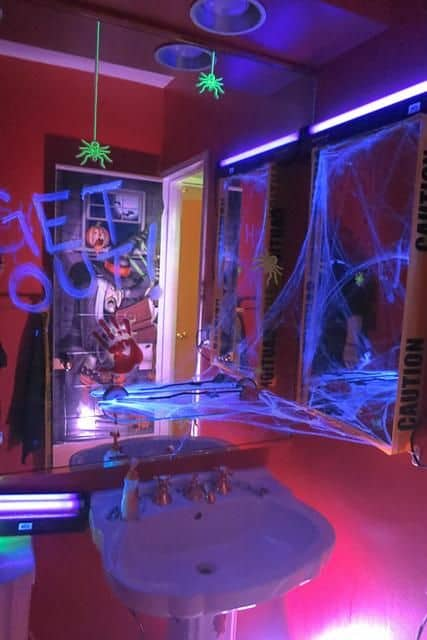 Replace bathroom lighting with black lights and bulbs to make your Halloween Bathroom decorations that much scarier