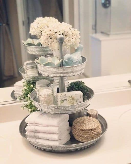 The best easy DIY Farmhouse small Bathroom decor ideas on a budget for apartments using glavanized tiered trays to organize counter top and provide storage