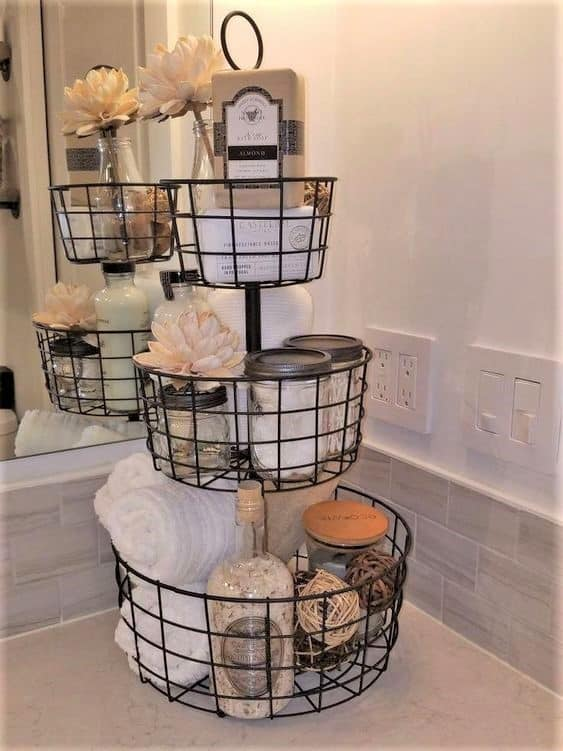 The best easy DIY Farmhouse small Bathroom decor ideas on a budget for apartments using tiered tray basket to organize counter top and give extra storage.