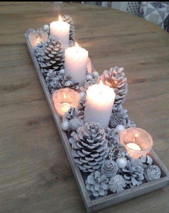 Breathtaking Farmhouse Glam Christmas Decor Ideas that'll transform your home - Rustic yet elegant winter painted pinecone centerpiece craft idea with candles #snowflakes