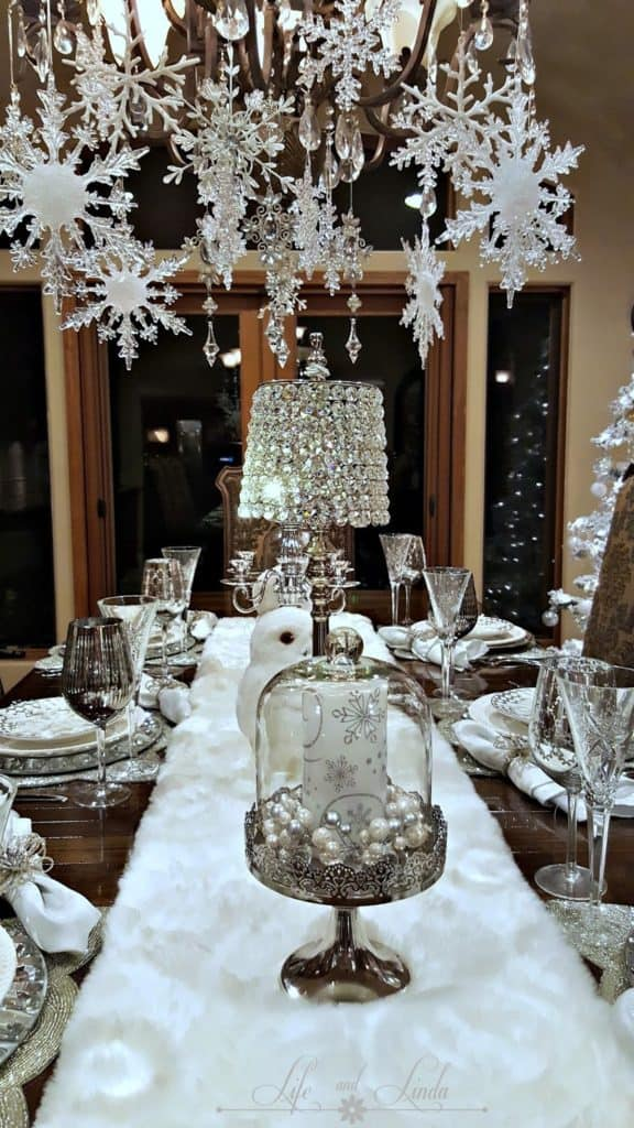 Easy DIY hanging snowflake chandelier winter decor idea using dollar store snowflakes and ribbon. Elegant Christmas decoration idea for mantle, window, ceiling, or wall. Great budget decor idea for the home, winter wedding, or Christmas party.