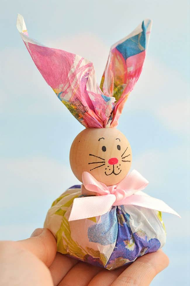 Easy DIY Paper Napkin Bunny Favors for kids using dollar store Items. The Best Easy DIY Easter Craft Decoration Ideas for a table or treat using a napkin and wooden bead.