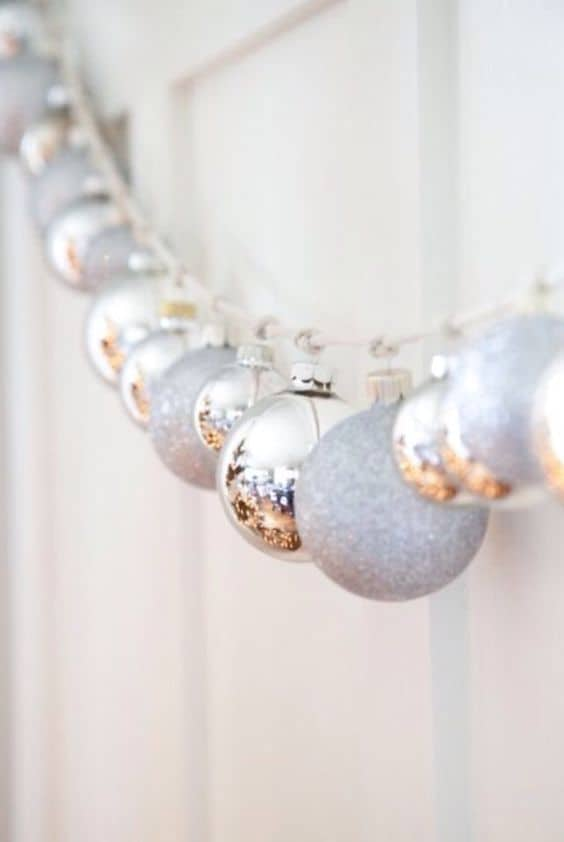 Easy DIY Christmas Garland idea on mantle or staircase using silver ornaments and string or ribbon. Elegant, budget home decor.