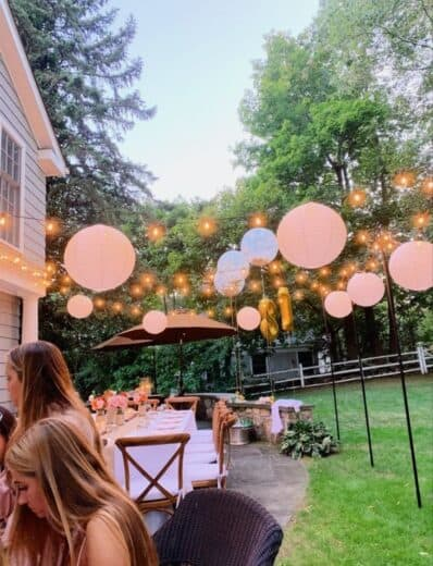 Lanterns and lights create a beautiful outdoor graduation party scene