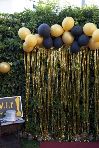 Easy DIY Graduation party decorations and picture ideas. Two cheap and easy methods for making a gorgeous photo backdrop or photo booth using dollar store streamers and balloons in black and gold.
