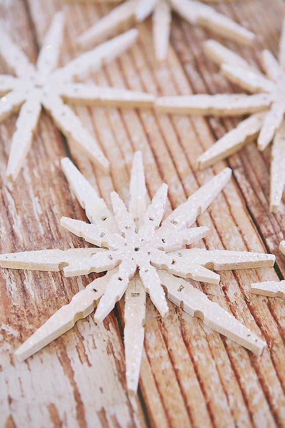 Easy DIY Popsicle Snowflake Christmas Ornament or Winter decoration. Simple yet beautiful dollar store craft gift idea anyone can make, even kids. Leave plain for a rustic farmhouse Christmas decoration or ornament or dress it up with paint, glitter, and rinestones. for elegant decor