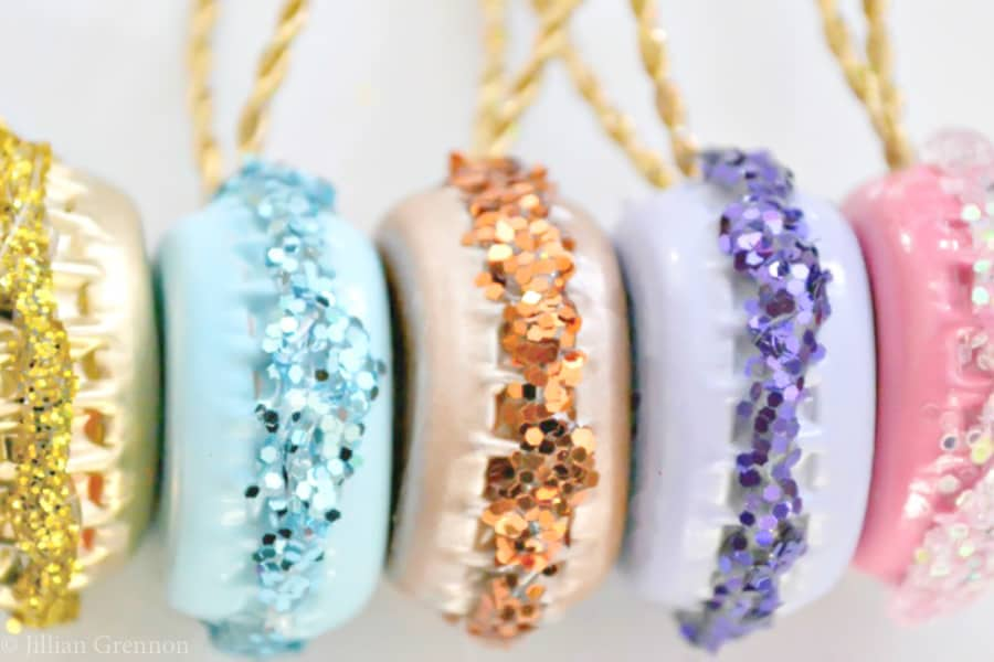 Easy DIY Glittery Macaron Ornaments That Look Professional and you'll actually want to keep. They are made with bottle caps, glue, glitter, and paint. An adorable craft or gift idea.